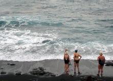 Grupp av äldre kvinnor i swimwearanseende som talar på en strand på royaltyfri fotografi