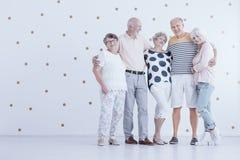 Grupp av äldre vänner som kramar sig i den vita studion med arkivfoto