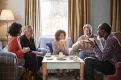 Grupp av åldriga vänner för mitt som möter runt om tabellen i coffee shop royaltyfria bilder