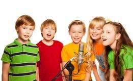Grupp av 8 år gammala ungar med mikrofonen Arkivfoton
