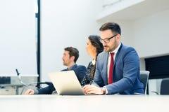 Grupp av affärsfolk i ett möte på kontoret som arbetar på datoren fotografering för bildbyråer