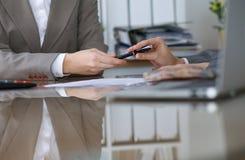 Grupp av affärsfolk och advokater som diskuterar avtalssammanträde på tabellen Kvinnachefen tar pennan för underteckning Arkivfoto