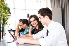 Grupp av affärsfolk som använder Digital apparater Team People som arbetar på deras tabell i modernt kontor Arkivfoton