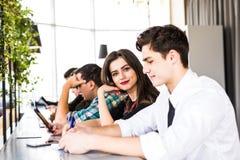 Grupp av affärsfolk som använder Digital apparater Team People som arbetar på deras tabell i modernt kontor Royaltyfri Foto