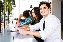 Grupp av affärsfolk som använder Digital apparater Team People som arbetar på deras tabell i modernt kontor Arkivfoto
