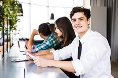 Grupp av affärsfolk som använder Digital apparater Team People som arbetar på deras tabell i modernt kontor royaltyfri fotografi