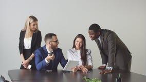 Grupp av affärsfolk som använder minnestavladatoren under ett möte arkivbild