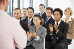 Grupp av affärsfolk som applåderar högtalaren på slutet av en presentation Arkivfoton