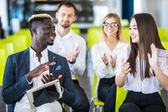 Grupp av affärsfolk som applåderar högtalaren på slutet av en presentation, konferens arkivbild