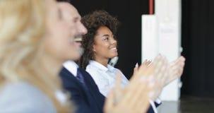 Grupp av affärsfolk som applåderar på konferensmötet, seminariumlyssnare som hälsar högtalaren som i regeringsställning applådera lager videofilmer