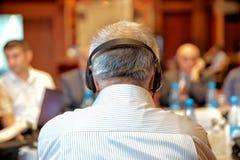 Grupp av affärsfolk som deltar i presskonferensen eller presentation Oigenkännligt folk som använder i örahörlurar för översättni arkivbilder