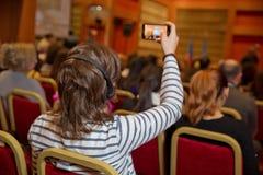 Grupp av affärsfolk som deltar i presskonferensen eller presentation Oigenkännligt folk som använder i örahörlurar för arkivbilder
