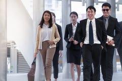 Grupp av affärsfolk som går och ler med kollegan på b Fotografering för Bildbyråer