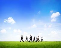 Grupp av affärsfolk som går till och med The Field i dagsljus Arkivfoto