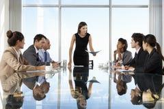 Grupp av affärsfolk som har styrelsemötet runt om den Glass tabellen arkivbilder