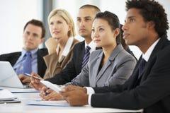Grupp av affärsfolk som lyssnar till kollegan som tilltalar kontorsmöte arkivfoto