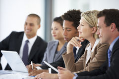 Grupp av affärsfolk som lyssnar till kollegan som tilltalar kontorsmöte arkivbilder