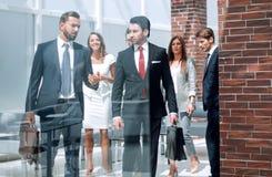 Grupp av affärsfolk som passerar till och med lobbyen av affärsmitten royaltyfri foto