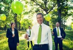 Grupp av affärsfolk som rymmer ballonger i skogen arkivfoton