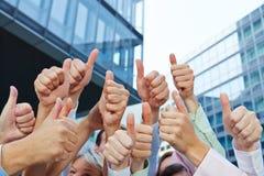 Grupp av affärsfolk som rymmer upp deras tummar Fotografering för Bildbyråer