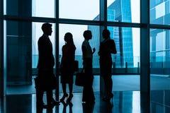 Grupp av affärsfolk som står i lobby eller korridor arkivbilder