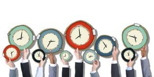 Grupp av affärsfolks händer som rymmer klockor royaltyfri bild