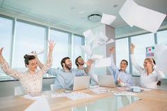Grupp av affärsledare som firar, genom att kasta deras affärslegitimationshandlingar i luften arkivbilder