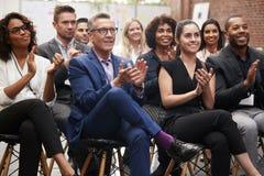 Grupp av affärsmän och affärskvinnor som applåderar presentation på konferensen royaltyfri bild