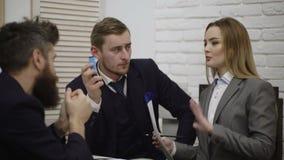 Grupp av affärsmän och affärskvinnor som har affärsmöte i regeringsställning Stilfulla ungdomari modernt kontor olikt arkivfilmer