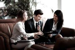 Grupp av aff?rsfolk som diskuterar dokumentet i bankkorridoren arkivfoto