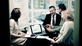 Grupp av aff?rsfolk som diskuterar ett viktigt dokument arkivfoton