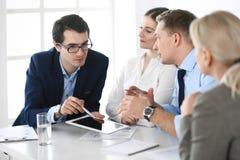 Grupp av aff?rsfolk som diskuterar fr?gor p? att m?ta i modernt kontor Chefer p? f?rhandling eller kl?ckningen av ideer arkivfoto