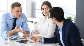 Grupp av aff?rsfolk som diskuterar fr?gor p? att m?ta i modernt kontor Chefer p? f?rhandling eller kl?ckningen av ideer arkivbild