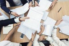 Grupp av aff?rsm?tet p? tabellen i det moderna kontoret, lagarbetet och de olika h?nderna som sammanfogar tillsammans aff?rsf?rh? arkivfoto