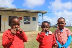Grupp av afrikanska barn som spelar munspelet utomhus i en lekplats, Swaziland, sydliga Afrika Royaltyfri Bild