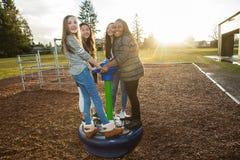 Grupp av aktiva barn som utanför spelar på skolalekplatsen Arkivbild