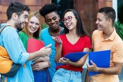 Grupp av amerikanska och latinska och afrikanska studenter som talar om läxa royaltyfria bilder