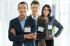 Grupp av anställda med tomma emblem som är stående upp för de royaltyfri bild