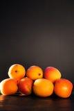 Grupp av aprikors på den mörka trätabellen på mörk bakgrund, mycket Royaltyfria Bilder