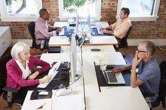 Grupp av arbetare på skrivbord i kontor för modern design arkivfoto