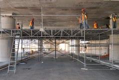 Grupp av arbetare som arbetar p? ett material till byggnadsst?llning i en parkeringsplats royaltyfri bild