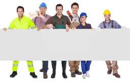 Grupp av arbetare som framlägger det tomma banret Arkivfoto