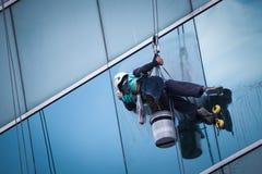 Grupp av arbetare som gör ren fönsterservice på hög löneförhöjningbyggnad Arkivbilder
