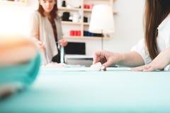 Grupp av arbete för två sömmerska i sömnadstudio affär isolerad liten white 3d Lag av den unga kvinnan som gör den idérika design Arkivbilder