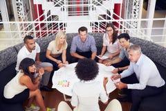 Grupp av arbetskollegor som har möte i en kontorslobby Royaltyfri Bild