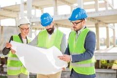 Grupp av arkitekter eller affärspartners som diskuterar golvplan på en konstruktionsplats fotografering för bildbyråer