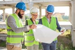 Grupp av arkitekter eller affärspartners som diskuterar golvplan på en konstruktionsplats arkivbilder