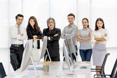 Grupp av 6 Asaina affärspersoner som tillsammans står i modernt av arkivbild