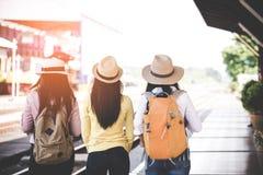 Grupp av asia kvinnor handelsresande och översikt för innehav för turistresanderyggsäck och att vänta i en plattform för drevstat Royaltyfri Bild