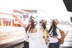 Grupp av asia kvinnor handelsresande och översikt för innehav för turistresanderyggsäck och att vänta i en plattform för drevstat Royaltyfri Foto